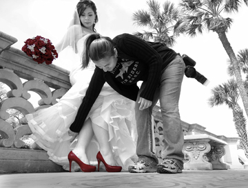 Show us your shoes. The official photographer adjusts the dress of Victoria Garcia to reveal her choice of footwear. Artist Statement: I desaturated the entire photo then colored back in the shoes and the flowers to emphasize the color. Photo by Mona Gallegos