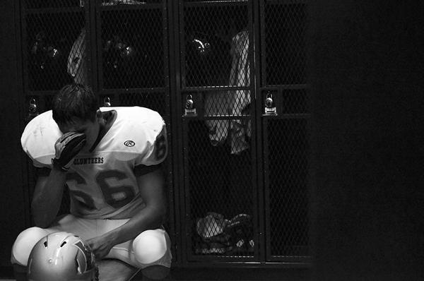 At halftime, Jacob Garza 12 sits on the bench in the locker room of Dragon Stadium, facing their first loss of the season. Garza, an offensive lineman, sits alone in the quiet as line backer, Paris Toler 12 yells, We did not come all the way over here to get our butts kicked. The frustration and dissapointment felt by Garza blocks all encouragement by his teammates. At 17-0, the possibilities of bringing in the first third consecutive win in 15 years seem slim. Photo by John Morgan