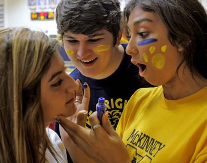 Before the game, juniors Vianei Sanchez and Cameron Coiro paint junior Myra Mata's face with school colors. The three students decided to wear the paint because the game was so important to the team.